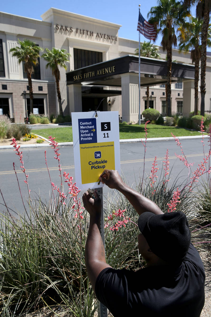 A worker who declined to give his name installs Curbside Pickup signs at the Fashion Show Mall ...