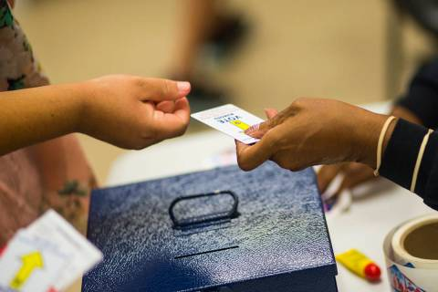 Louise Daniels, right, takes voting cards from voters at a polling station at Doolittle Communi ...