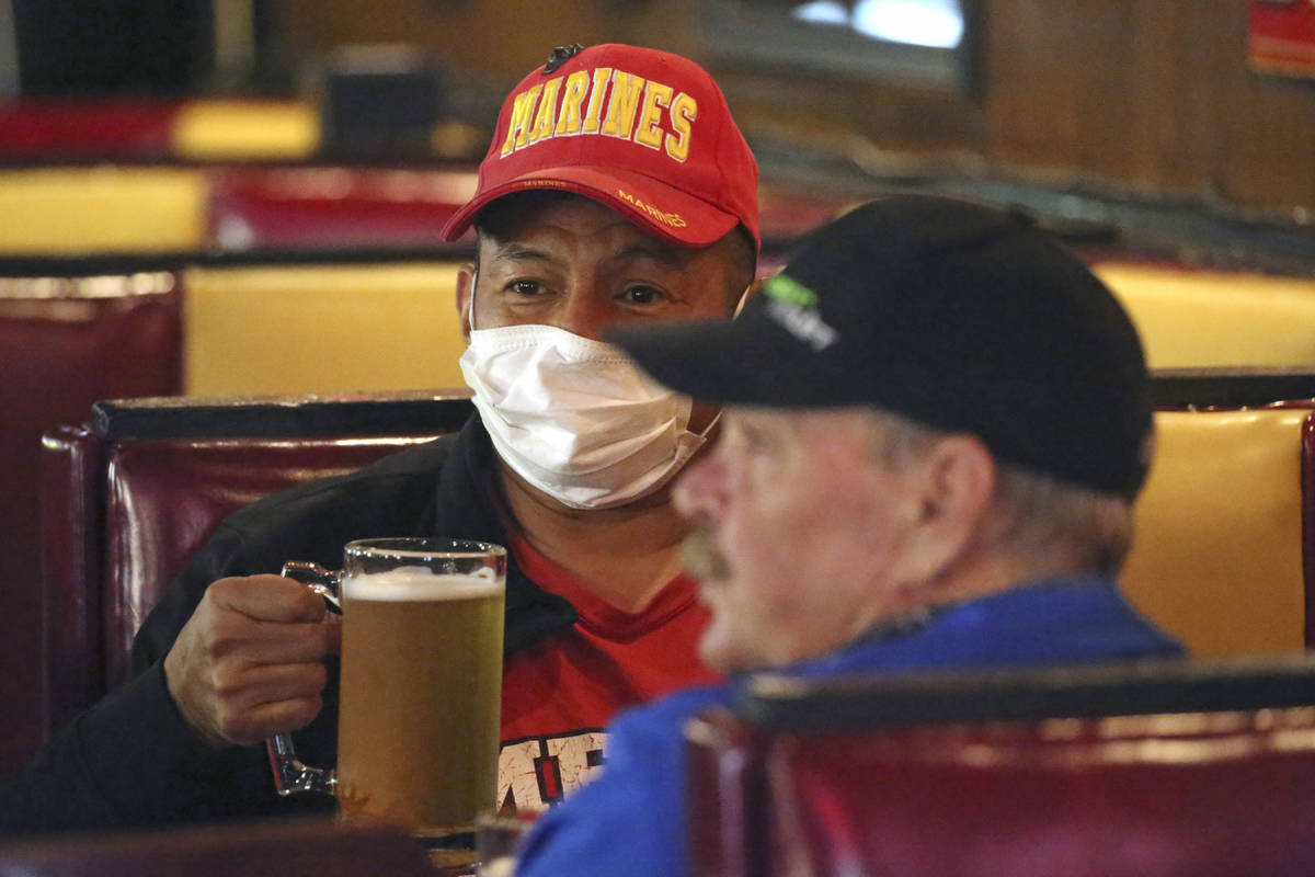 Cheers to You patron Clifford Pesheep, left, wears a mask before drinking his beer at the bar F ...