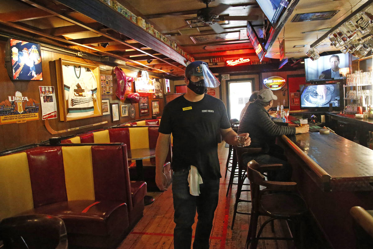 Cheers to You bartender Andrew Lohry wears a mask and face shield after the bar opened Friday m ...