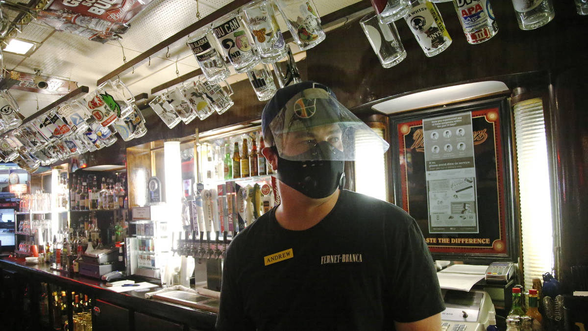 Cheers to You bartender Andrew Lohry wears a mask and face shield behind the bar Friday, May 1, ...