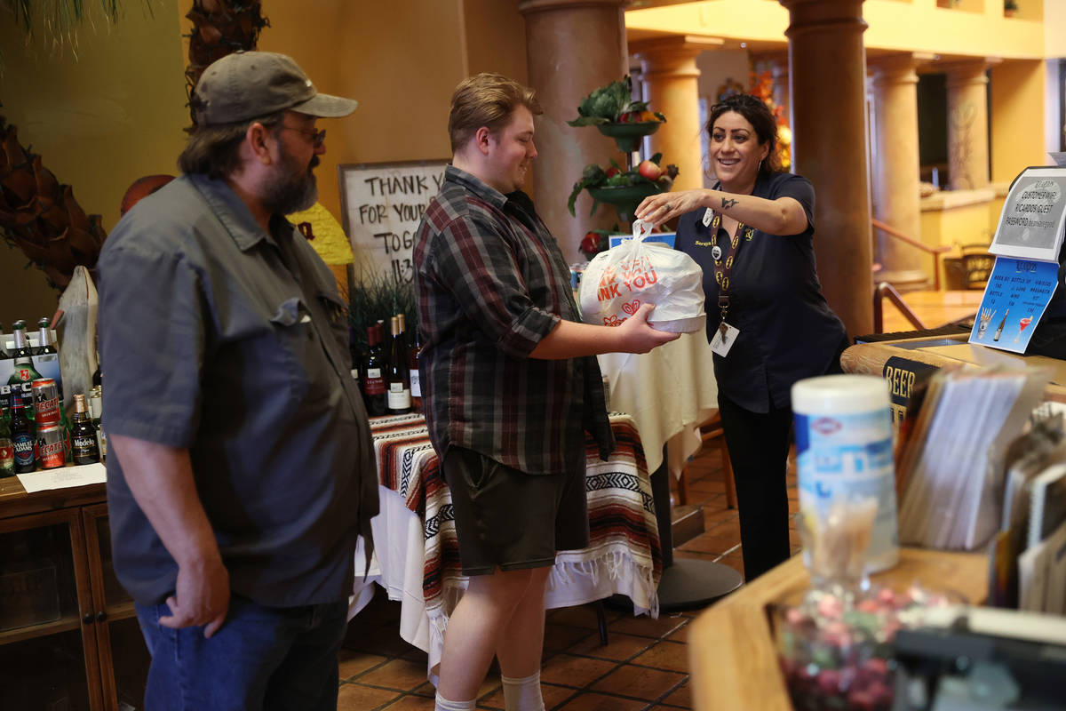 James Redensek, from left and his son also James, pick up their food order from restaurant mana ...