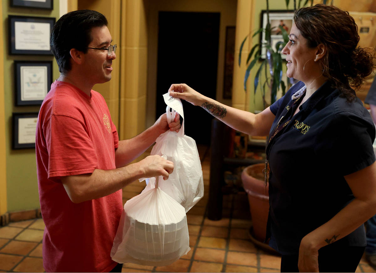 Mike O'Brien of Las Vegas, left, picks up his food order from restaurant manager Soraya Amaral ...