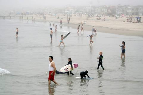 Swimmers and surfers wade in the water Sunday, April 26, 2020, in Newport Beach, Calif. (AP Pho ...