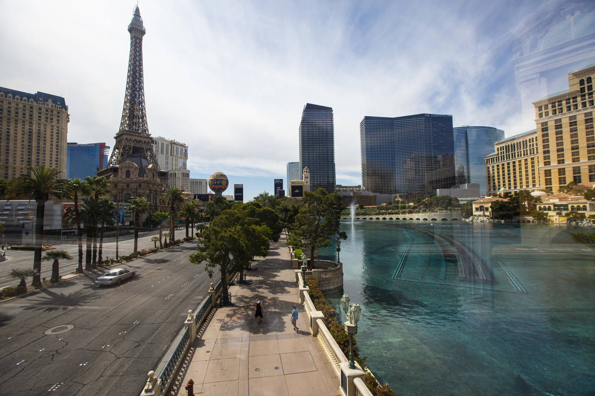 People pass by the Bellagio while walking the Las Vegas Strip on Thursday, April 16, 2020. (Cha ...