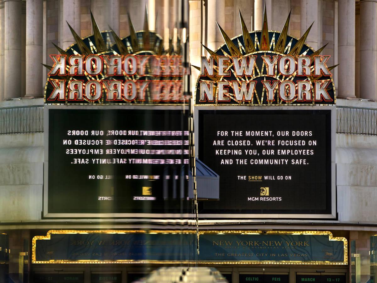 A New-York New-York sign is reflected in pedestrian bridge glass along Las Vegas Boulevard on t ...