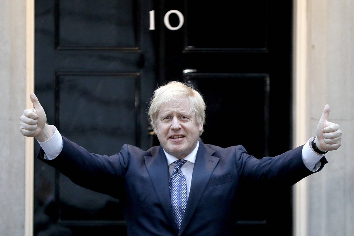 Britain's Prime Minister Boris Johnson shows thumbs up before he applauds on the doorstep of 10 ...