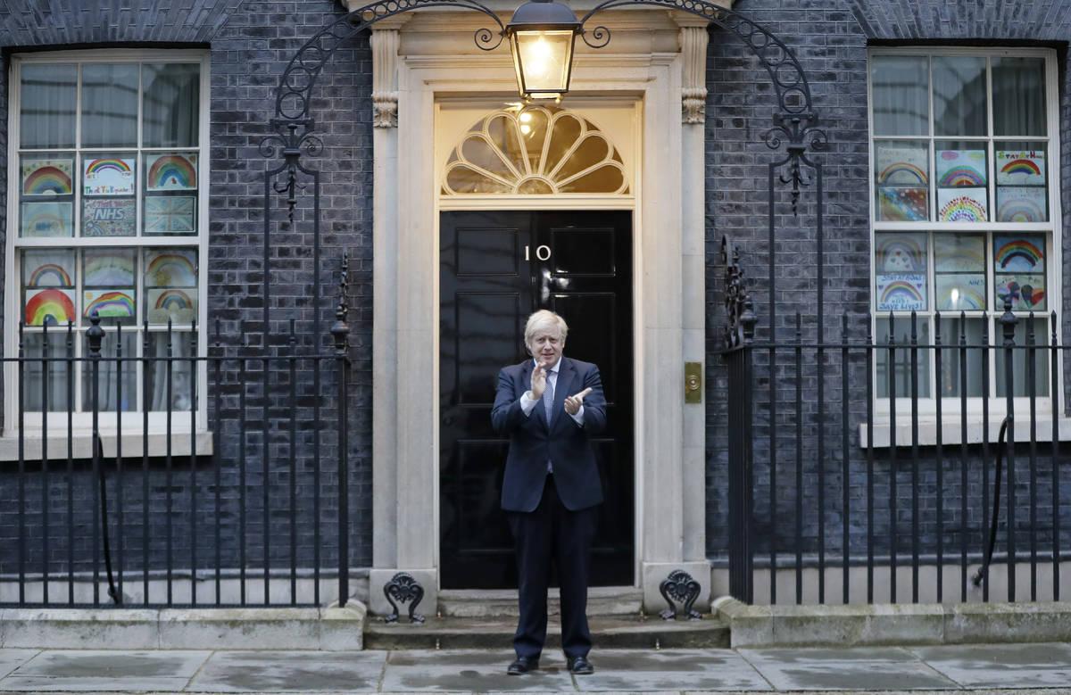 Britain's Prime Minister Boris Johnson applauds on the doorstep of 10 Downing Street in London ...