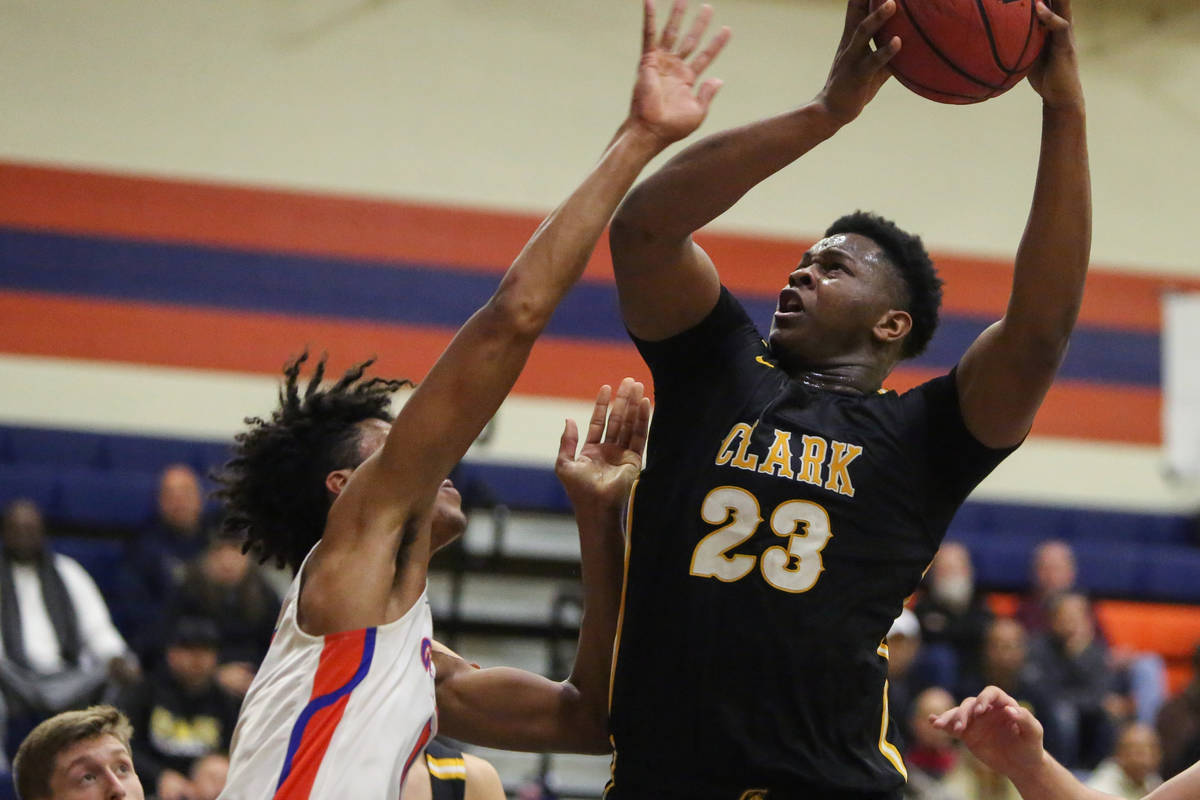 Clark's Antwon Jackson (23) goes to shoot the ball while under pressure from Bishop Gorman's Is ...