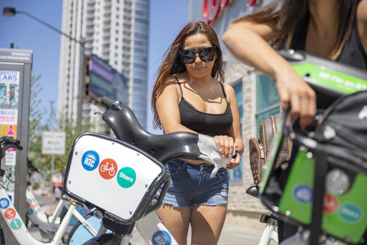 Maribel Leyva sanitizes her rented RTC Bike Share from the East Sahara Ave., and Las Vegas Blvd ...