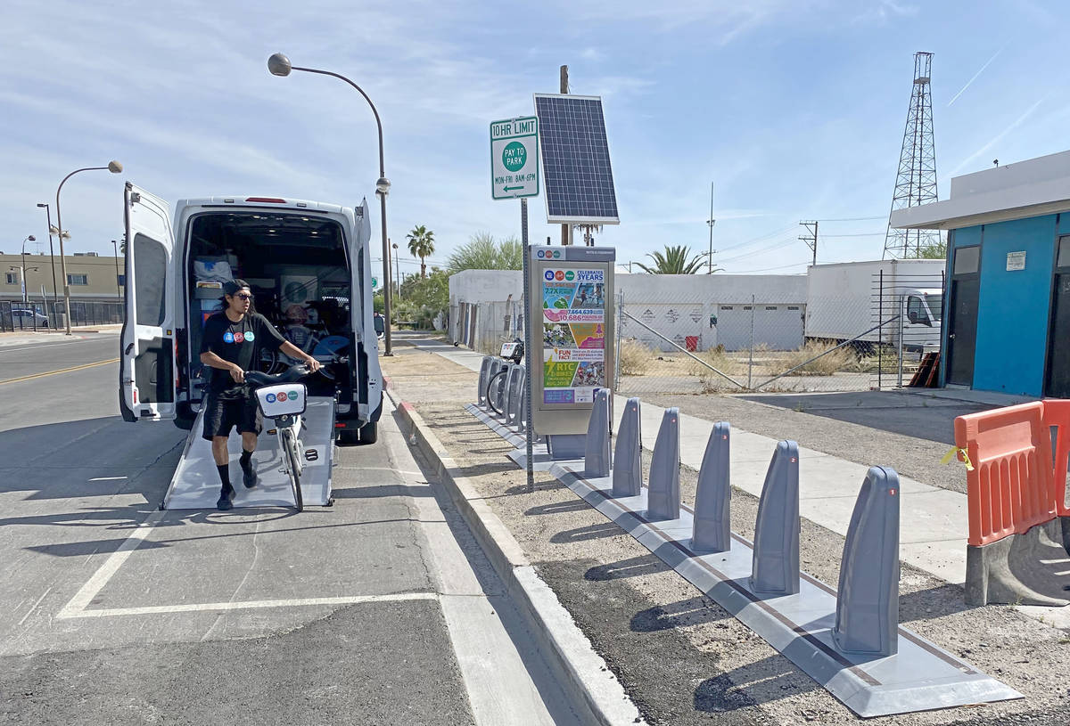 A Regional Transportation Commission worker reloads an empty RTC Bike Share station on the corn ...