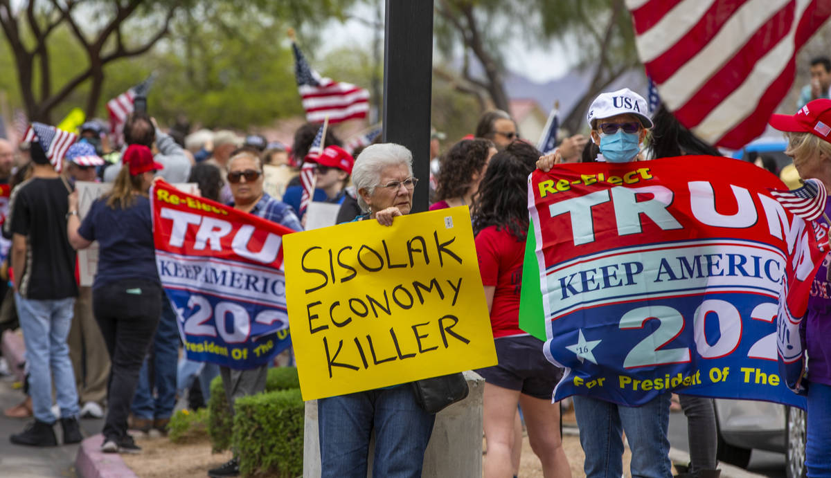 Carmen Rhoda, center, carries bright sign while joining the many others during the Re-Open Neva ...