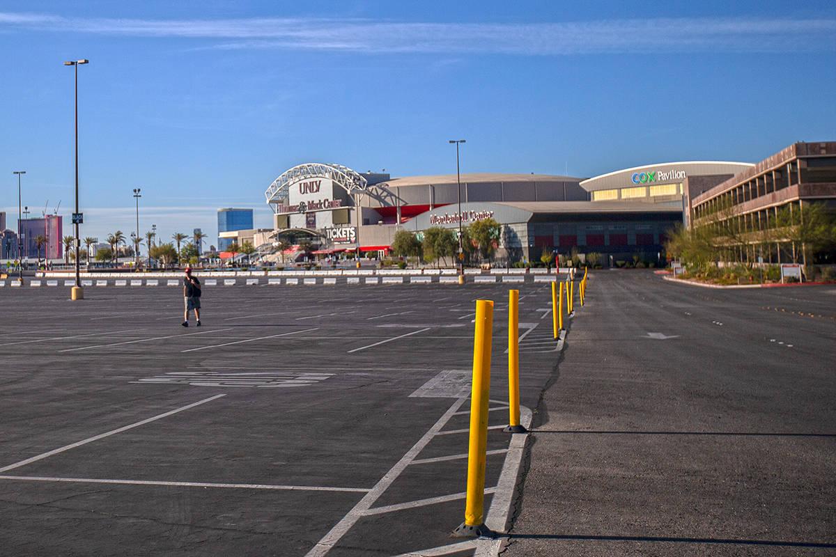 A single pedestrian walks through the empty parking lot of the Thomas & Mack Center on Satu ...