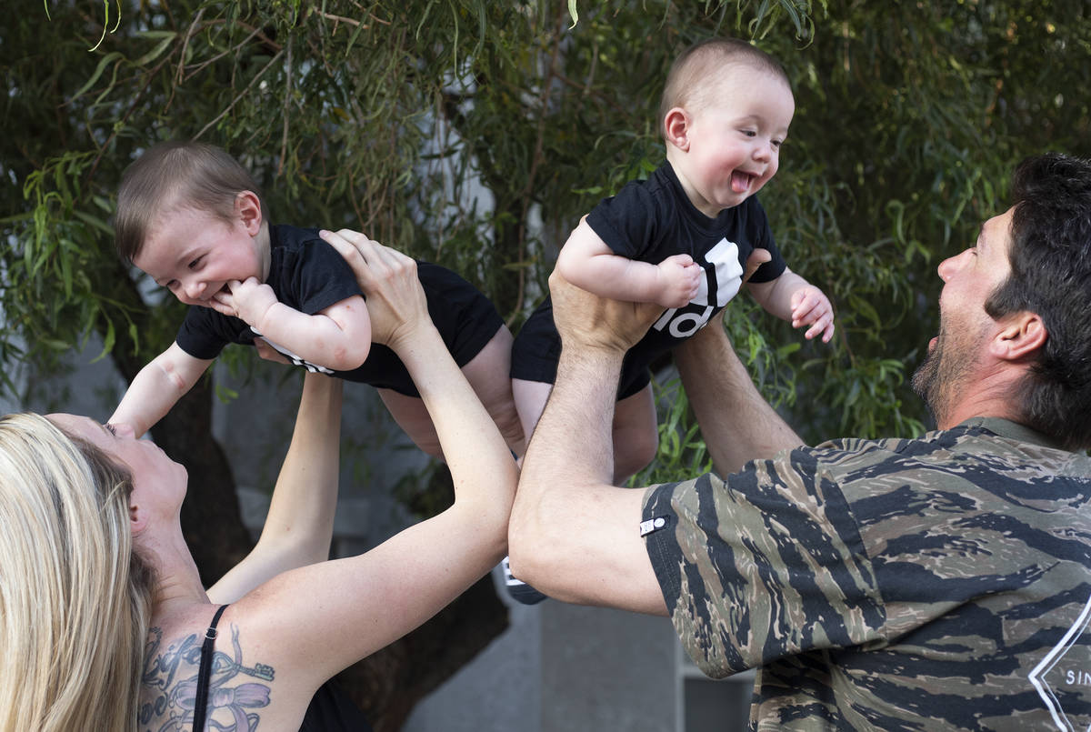 Shannon and David Belford play with their 9-month-old twin sons, Gavin and Garrett, outside the ...