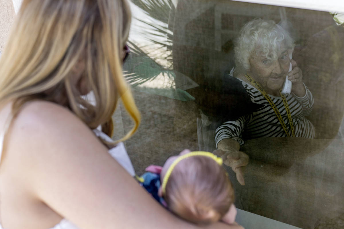 June Watkins, 97, reaches out for her one-month-old great granddaughter, Eliana, as her grandda ...
