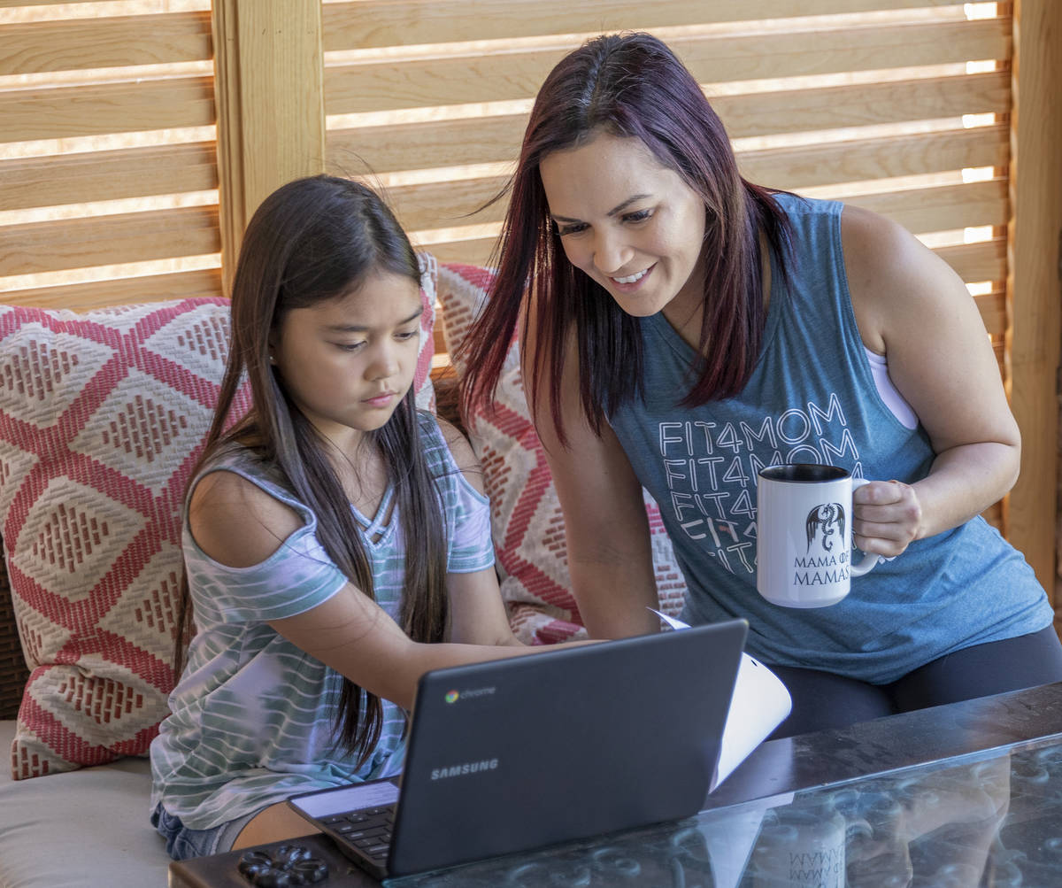Owner of FIT4MOM Las Vegas Jessica Peralta helps her daughter Grace, 9, with her online schooli ...