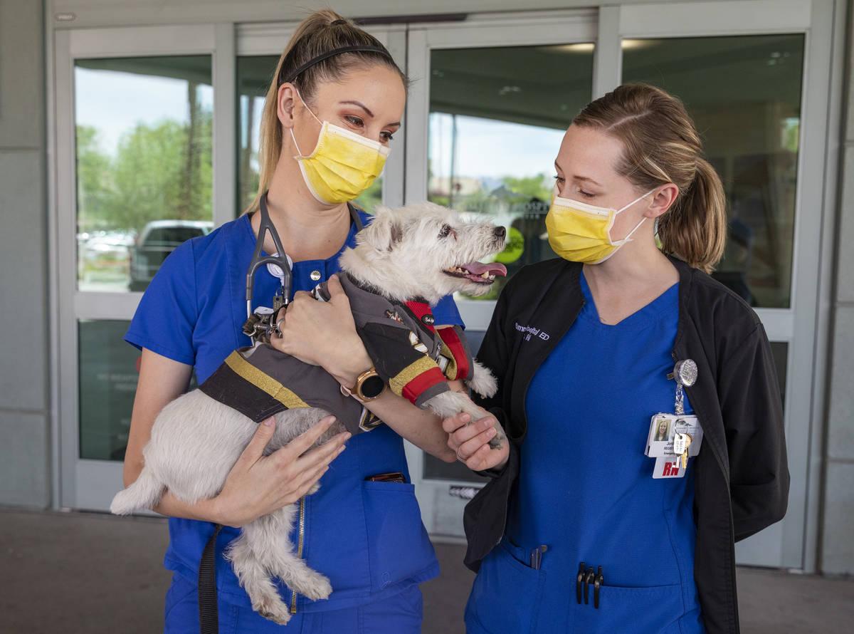 Emergency room registered nurses Kelsey Balton, left, and Jordon Connell, hold Bark-Andre Furry ...