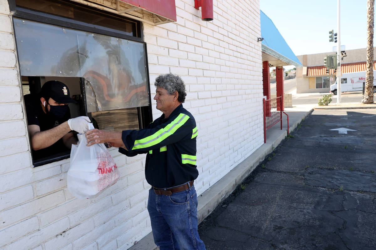 Uvaldo Covian, 30, who owns Roy's Cafe with his family, delivers food to Joel Valenzuela, 65, o ...