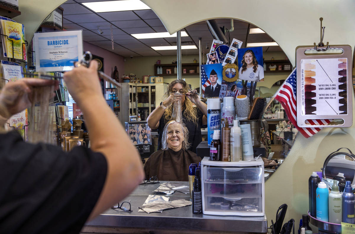 Owner Stephanie Wilkerson, top, cuts the hair of customer Louise Bustillos as business resumes ...