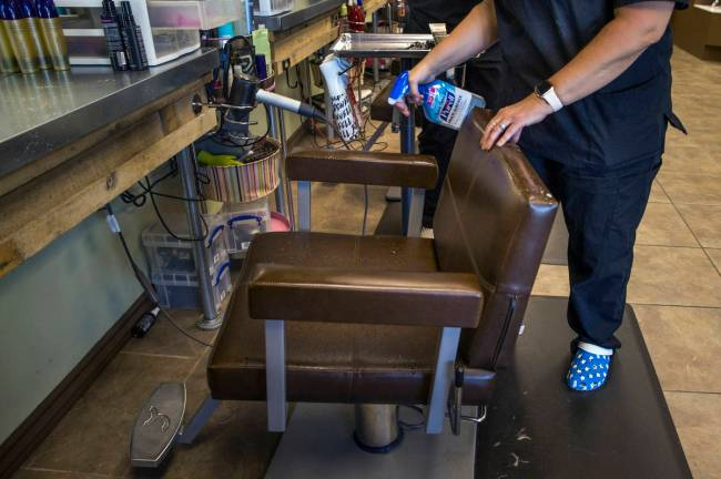 Owner Stephanie Wilkerson regularly sanitizes her station for the next customer as business as ...
