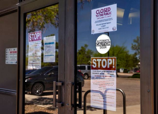 A variety of warning signs posted on the front of the Kingman Police Department during the coro ...