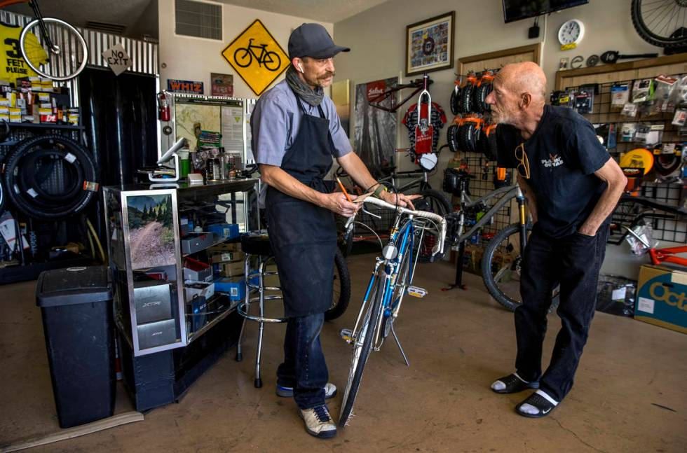 SpokesMann bicycle shop owner Ed Mann, left, talks about the repairs recommended to customer Ma ...