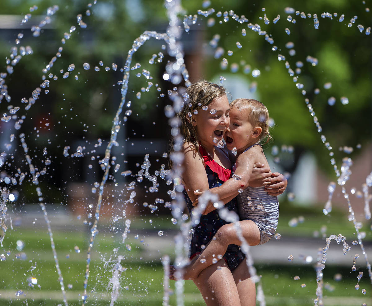 Skye Moyle, left, holds sister Demi, 2, as they play in the fountains at Town Square Park on Tu ...