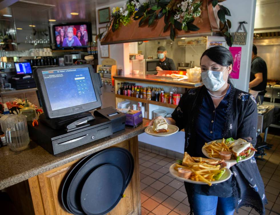 Server Katherine Warden, right, wears a medical mask while delivering food to one of her tables ...