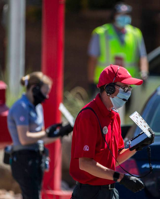 Chick-fil-A employees wearing medical masks take drive through orders on Tuesday, May 5, 2020, ...