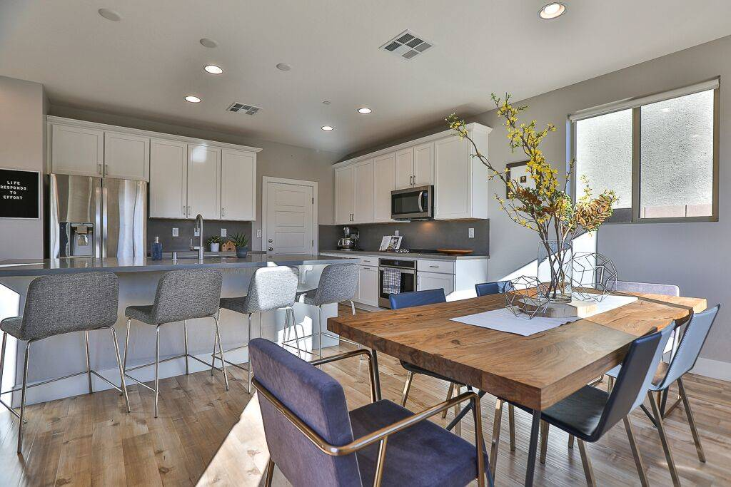 The dining area is off the kitchen had has a modern look and a grey and white palette. (Life Re ...