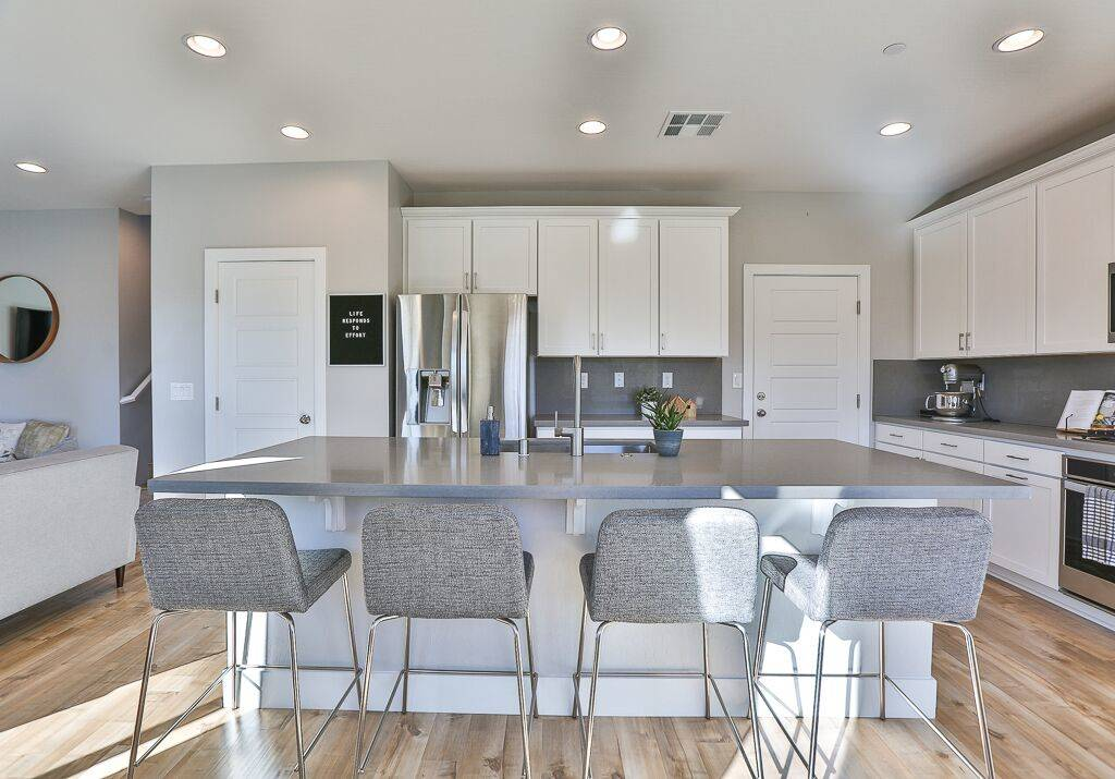 The kitchen has a large center island with plenty of seating for guests. (Life Realty)