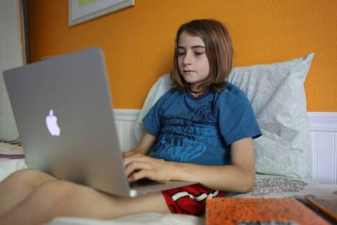 Levi Finfrock, a fifth-grade student at The Alexander Dawson School, does schoolwork at home. ( ...