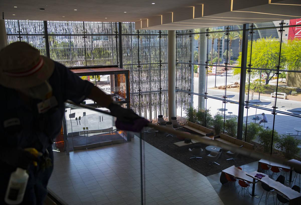 Custodian Jarrell Siler sanitizes handrails in the Hospitality Hall at UNLV in Las Vegas, Thurs ...