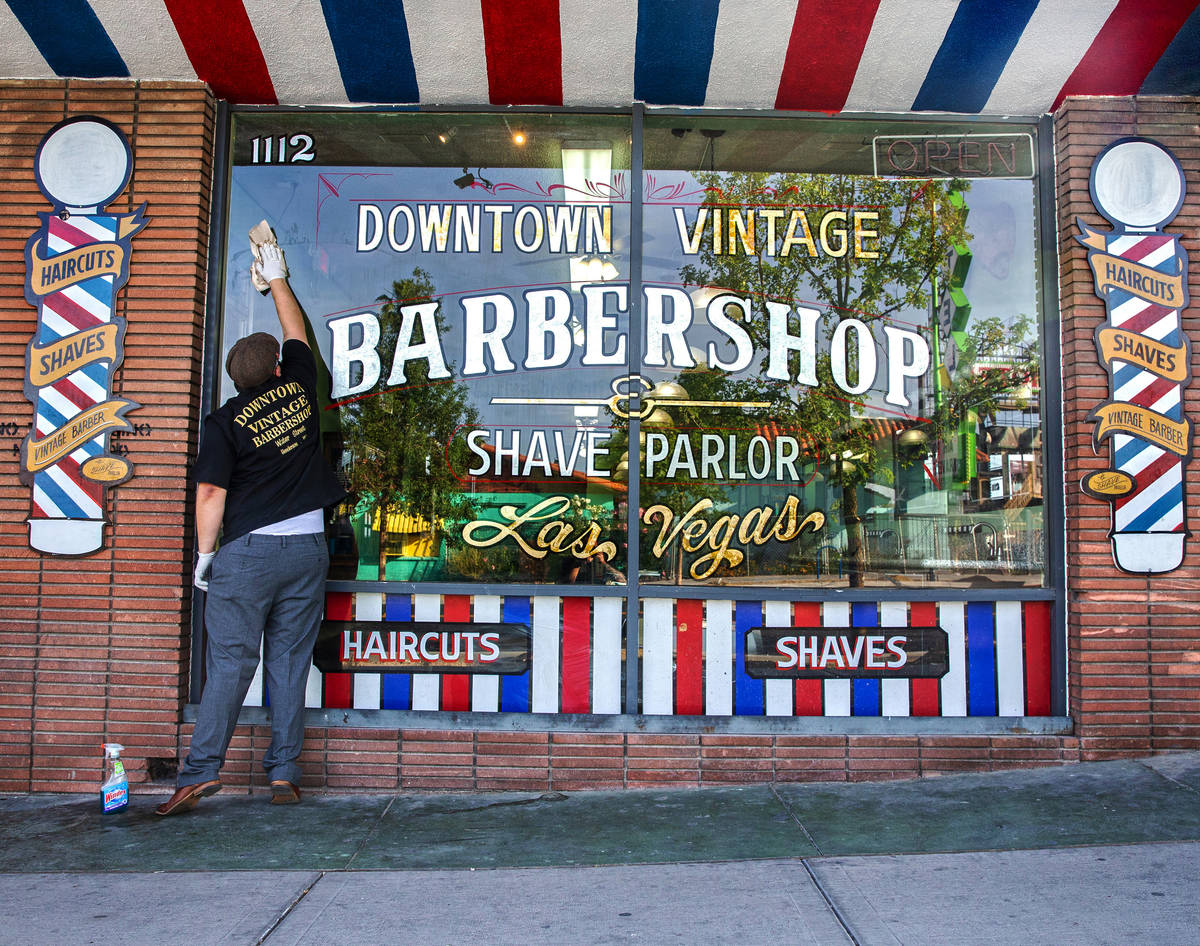 Jorge Reyes, owner of Downtown Vintage Barbershop, cleans his storefront in preparation to open ...