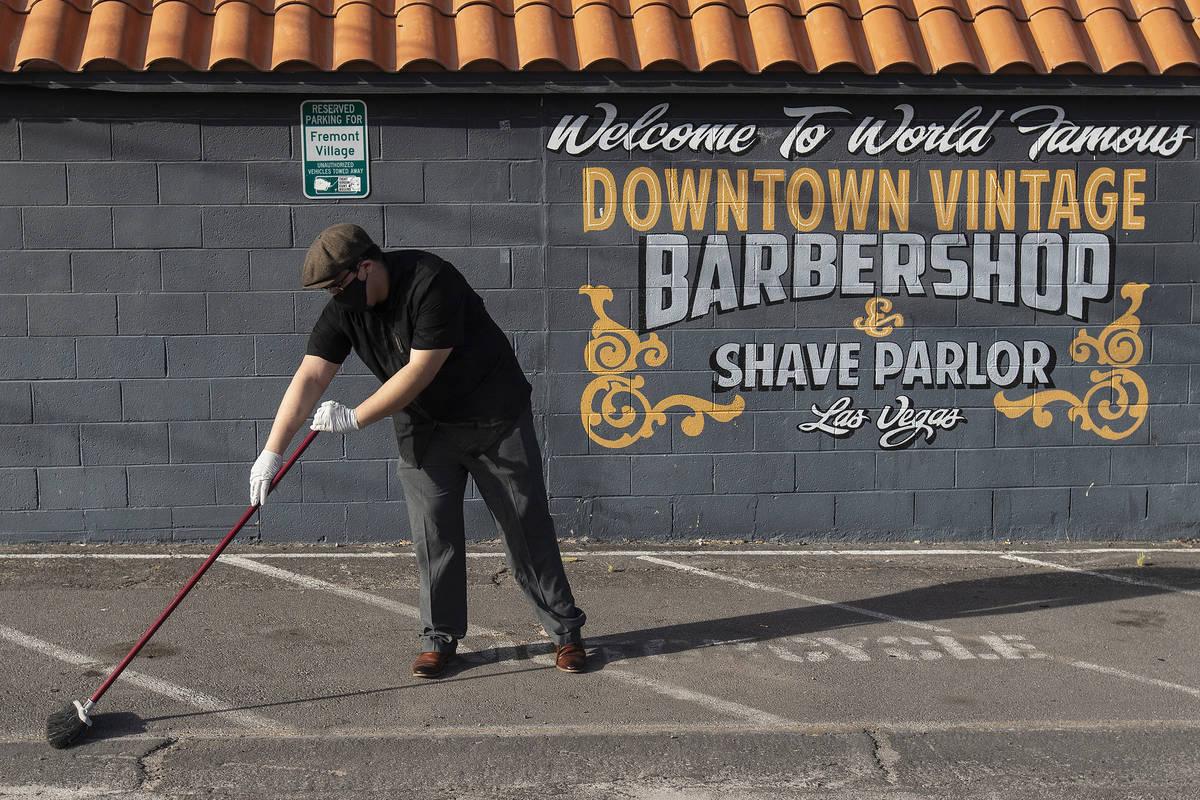 Jorge Reyes, owner of Downtown Vintage Barbershop, sweeps in back of his business in preparatio ...