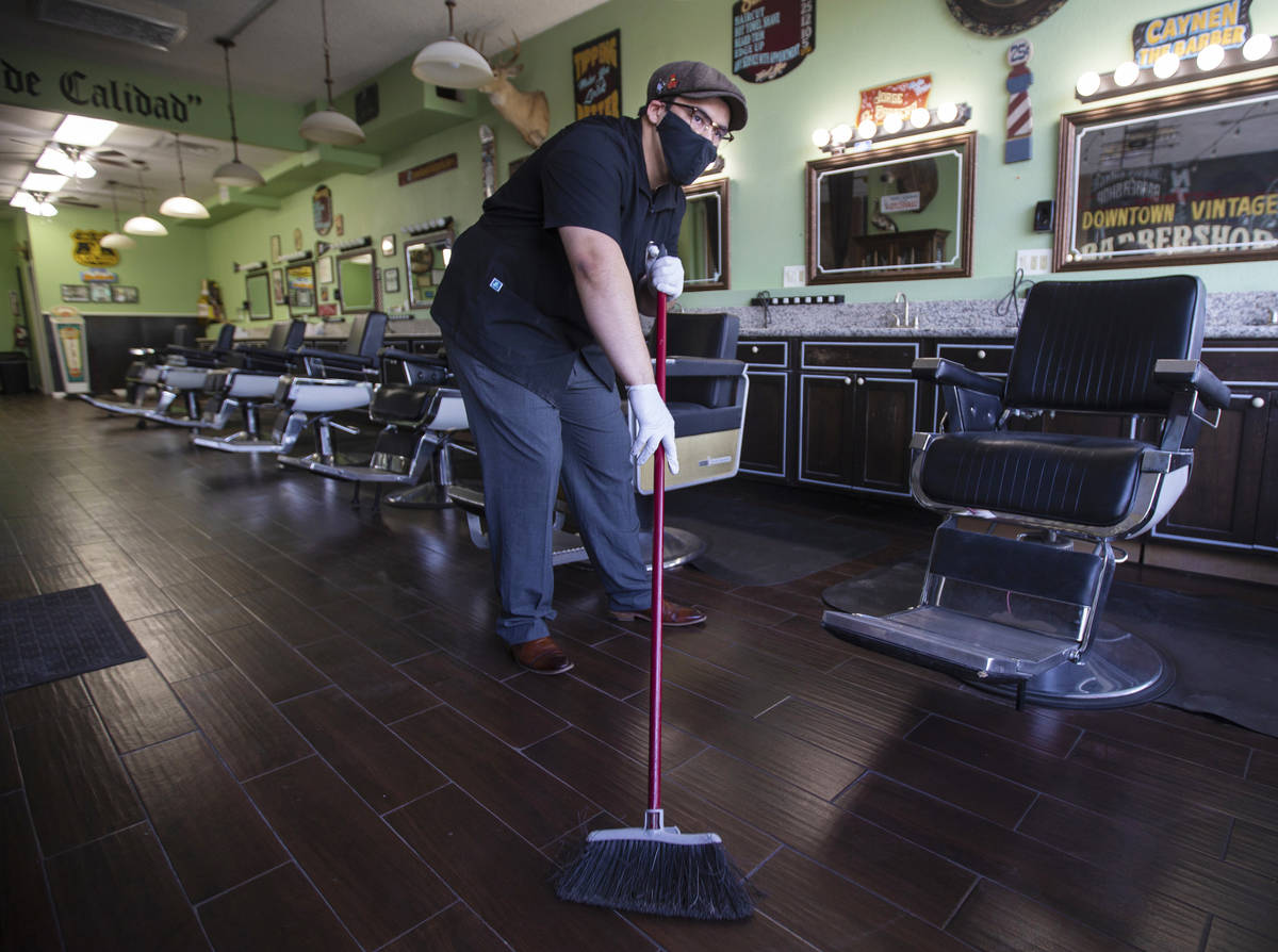 Jorge Reyes, owner of Downtown Vintage Barbershop, sweeps inside his business in preparation to ...