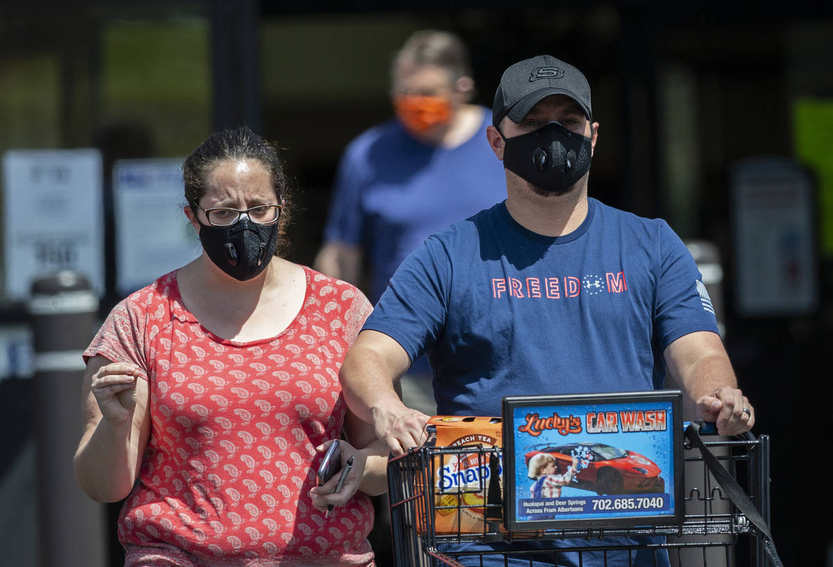 Shoppers wear protective masks as they leave Albertsons in northwest Las Vegas on Thursday, May ...