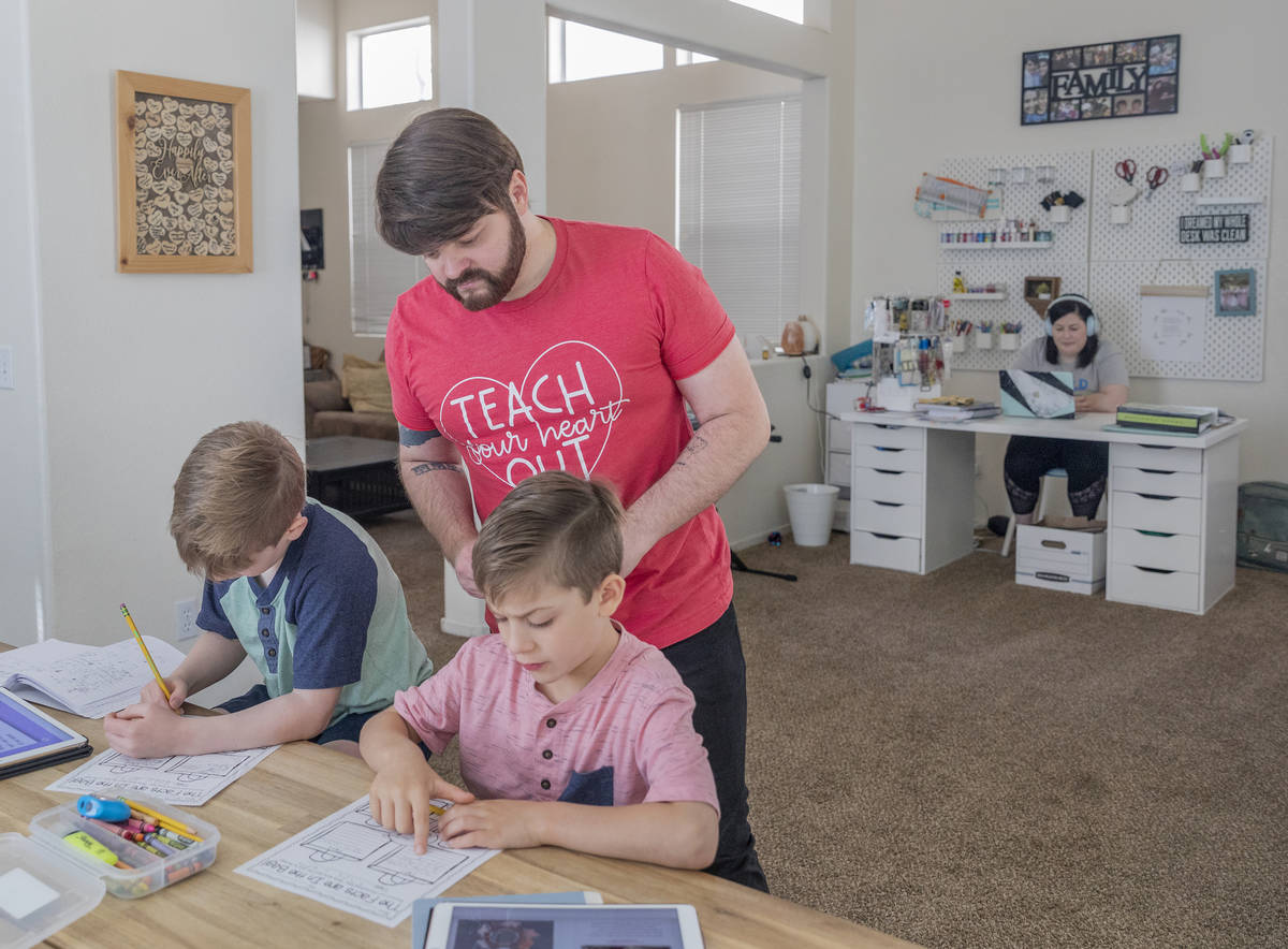 Twins Everett, left, and Atticus Mayville, 7, work on a school project as their mom, a middle s ...