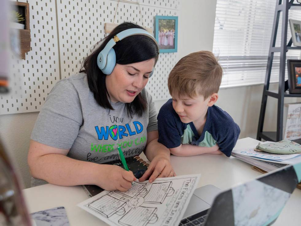 School counselor for Jerome Mack Middle School Jessica Houchins, left, helps her son Everett Ma ...