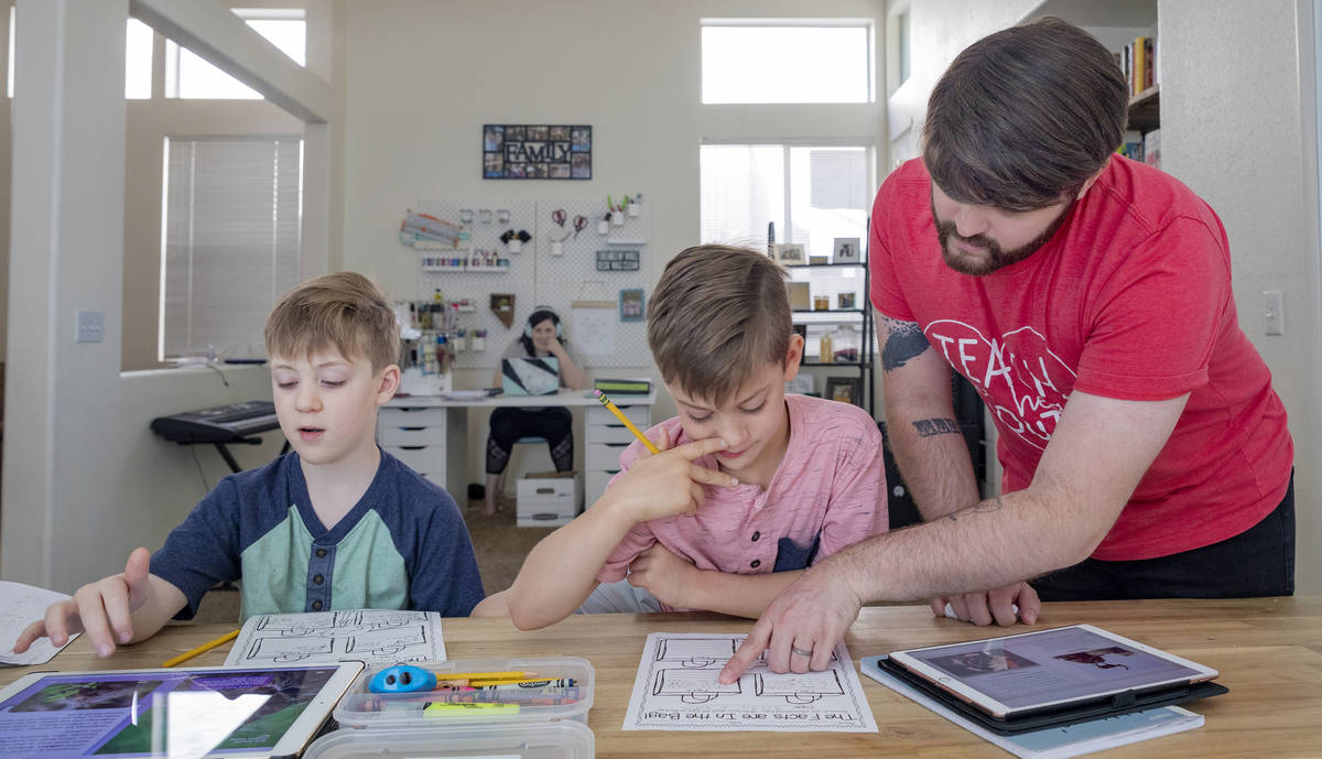Twins Everett, left, and Atticus Mayville, 7, work on a school project with help from stepfathe ...