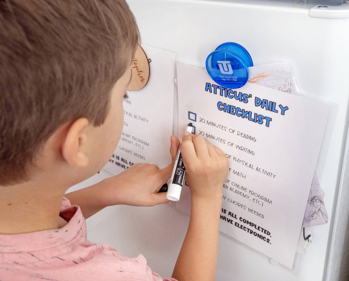 Atticus Mayville, 7, crosses off his school checklist at his home in Henderson on Thursday, May ...