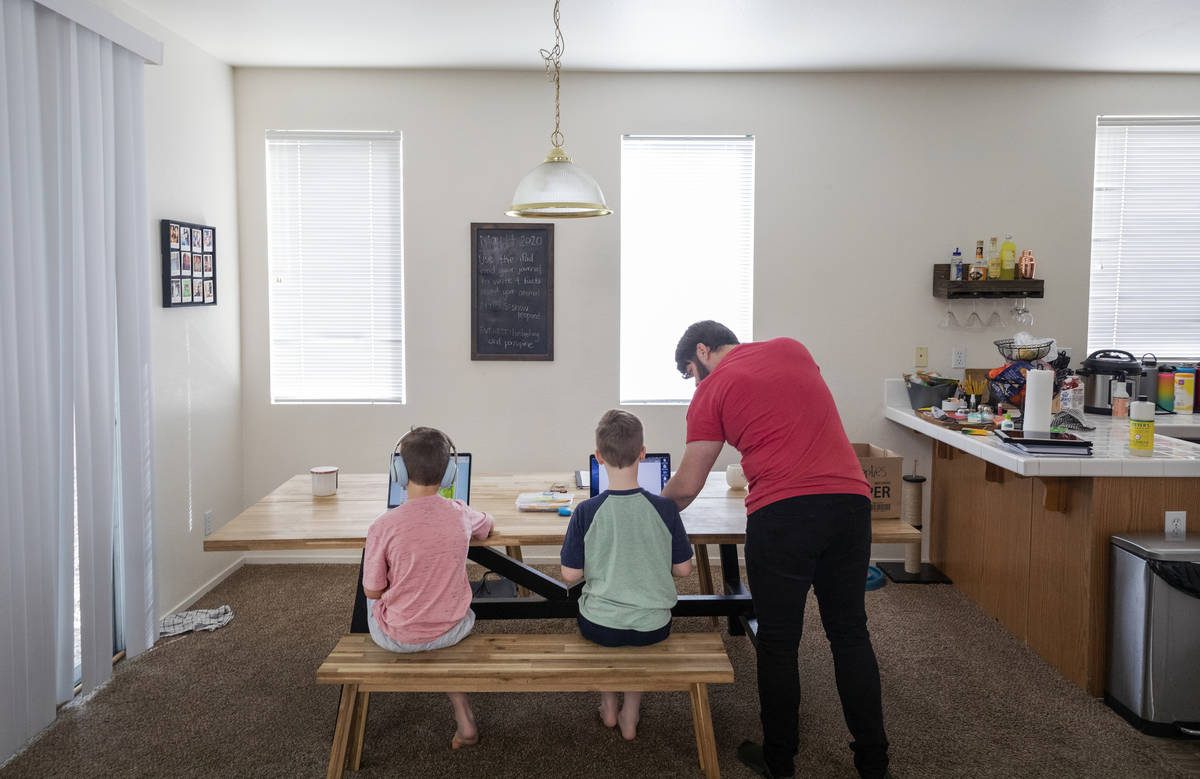 Atticus Mayville, 7, left, and Everett Mayville, 7, work on school projects with help from thei ...