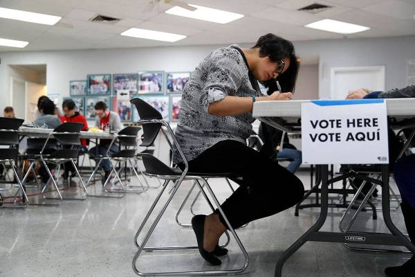A woman votes at an early voting location at the culinary workers union hall, Saturday, Feb. 15 ...