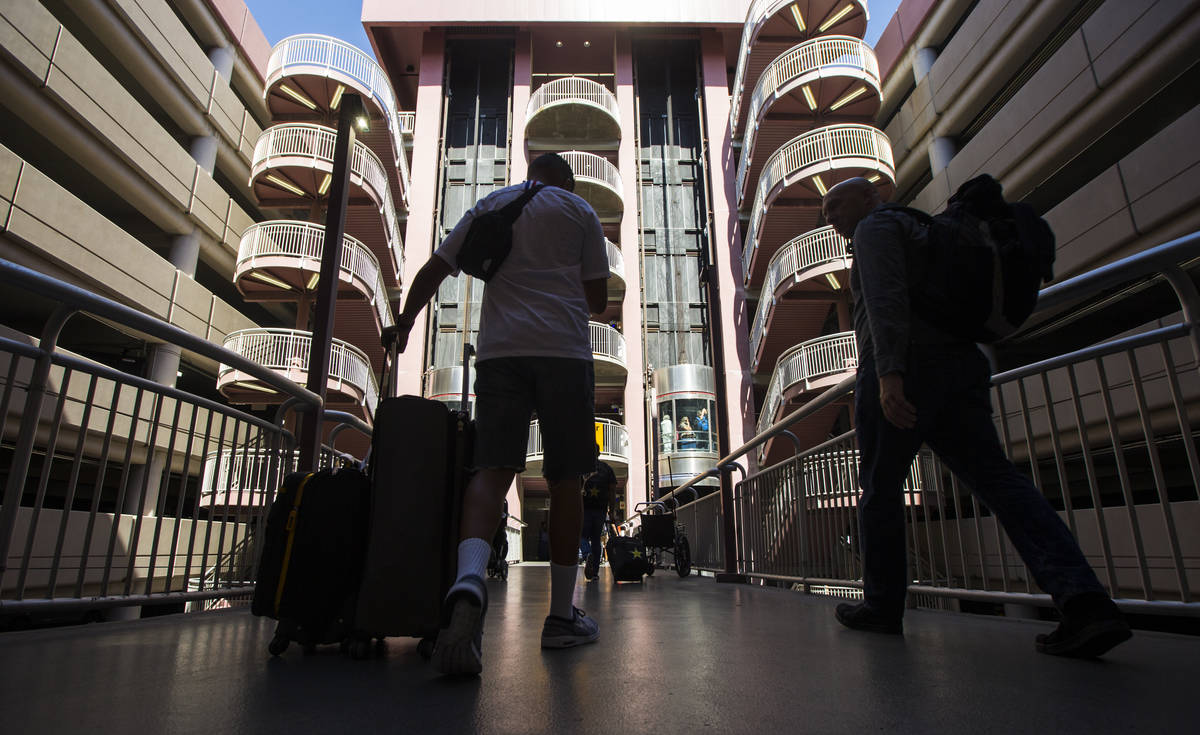 Passengers make their way to rideshare services and parking after arriving at McCarran Internat ...