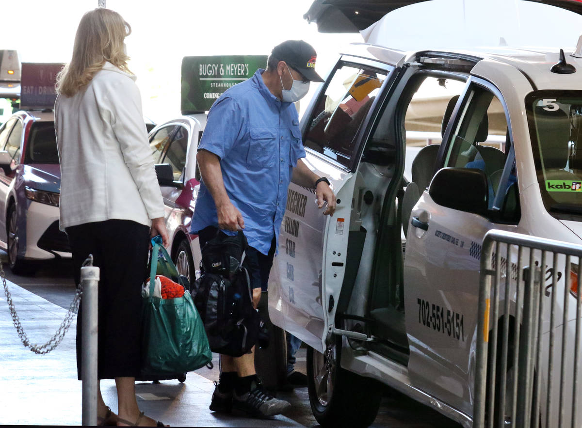 Arriving passengers at McCarran International Airport take a taxi on Thursday, May 7, 2020, in ...