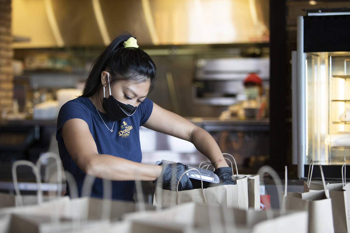 Juliana Asa fills a to-go order at Nora's Italian Cuisine on Wednesday, May 6, 2020, in Las Veg ...
