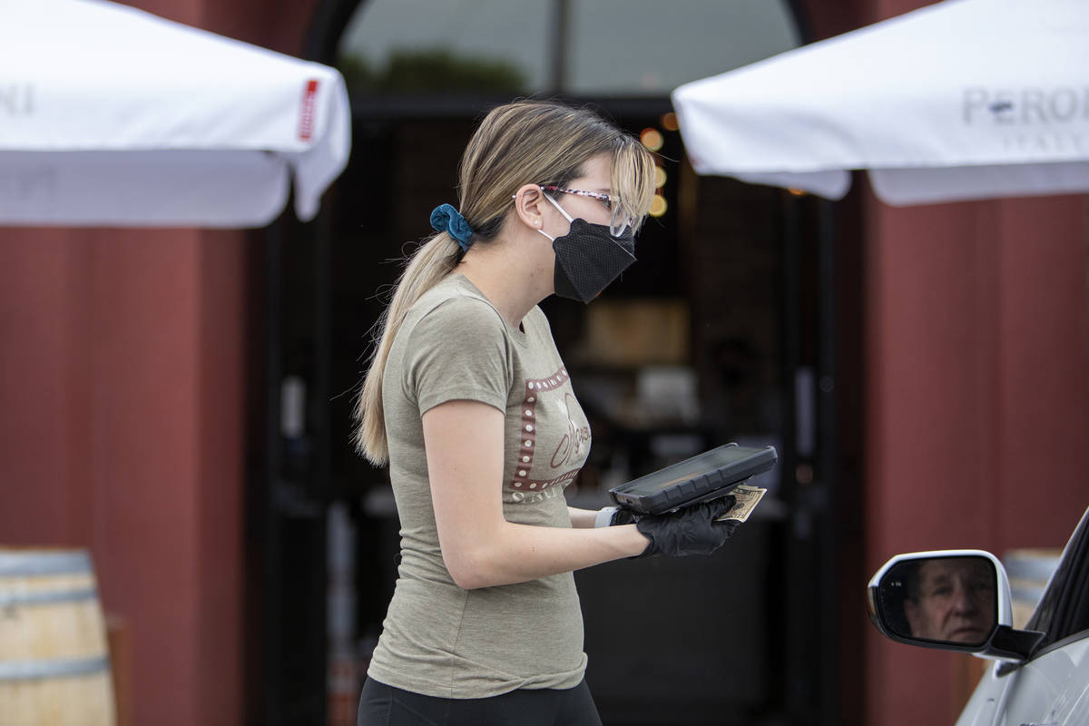 Michelle Villalpando takes payment for Ted Powell's curbside pickup order at Nora's Italian Cui ...