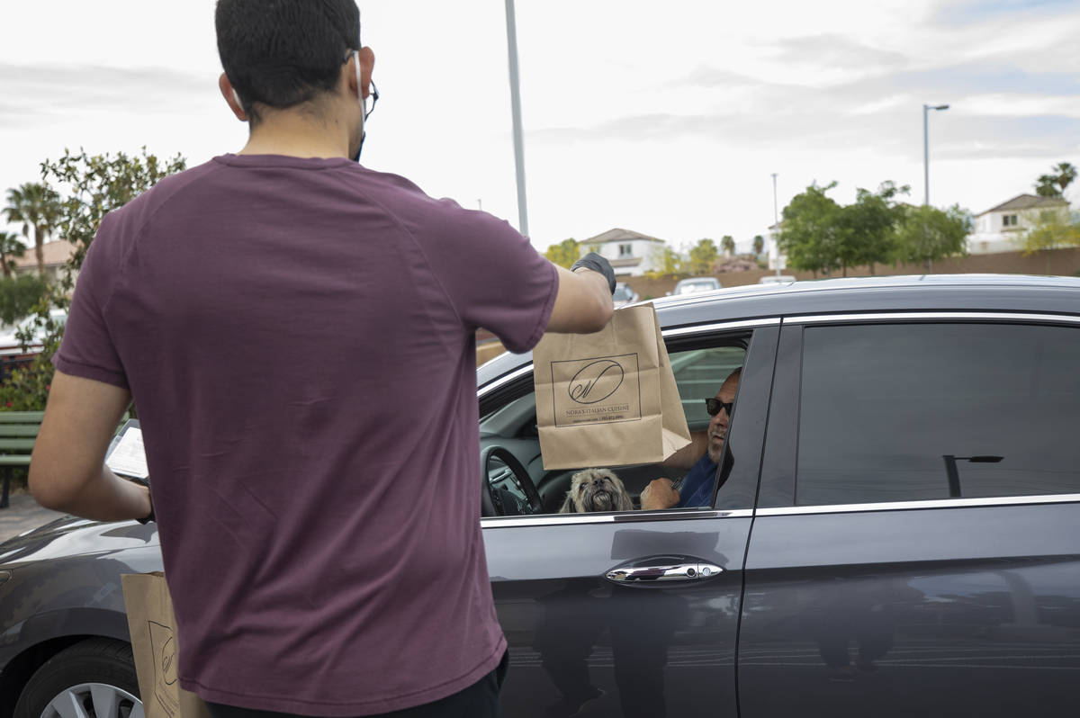 Anthony Campos hands Gil Jordan his curbside pickup order at Nora's Italian Cuisine on Wednesda ...