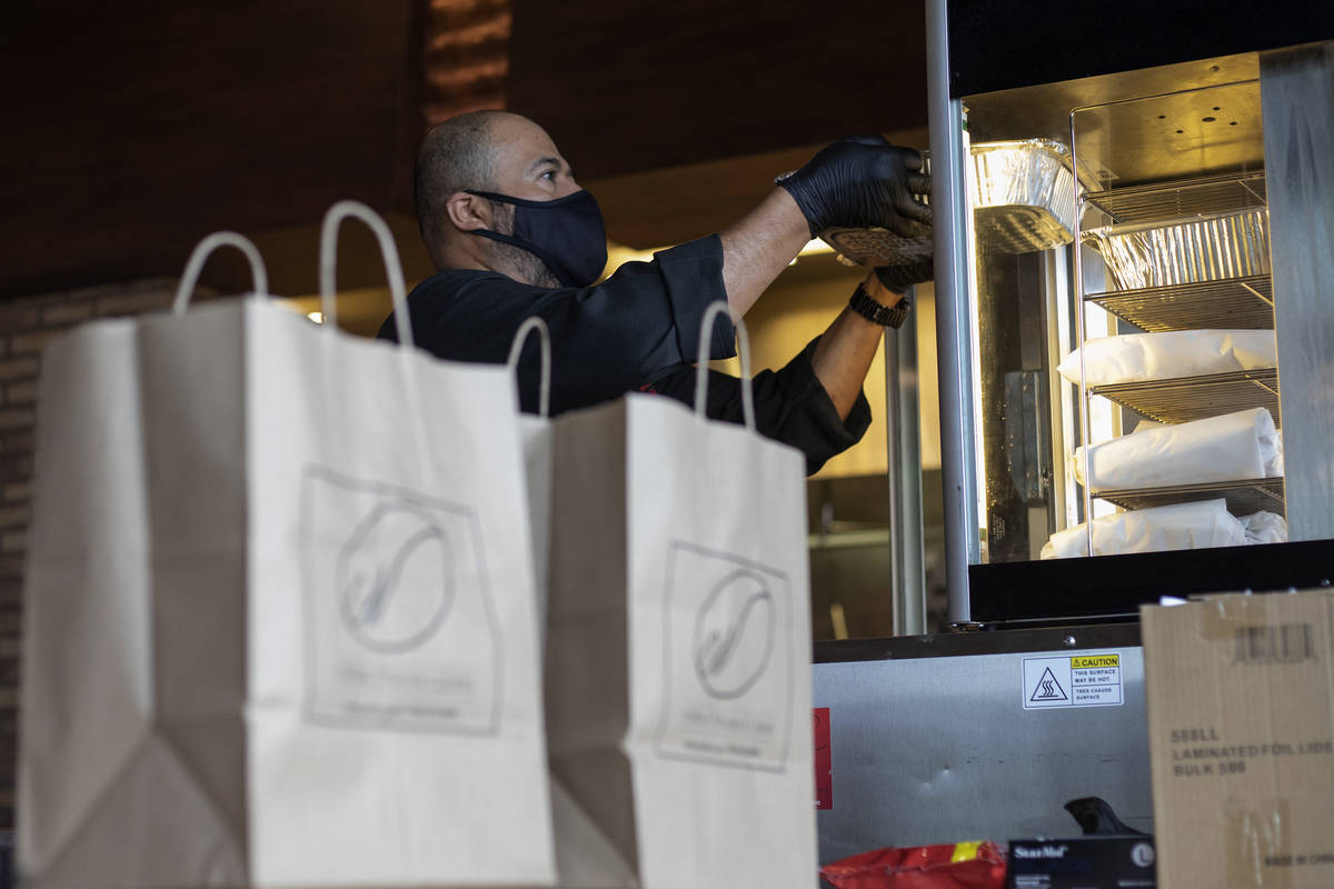 Misael Macias puts hot meals in a hot box as curbside pickup orders await customers at Nora's I ...