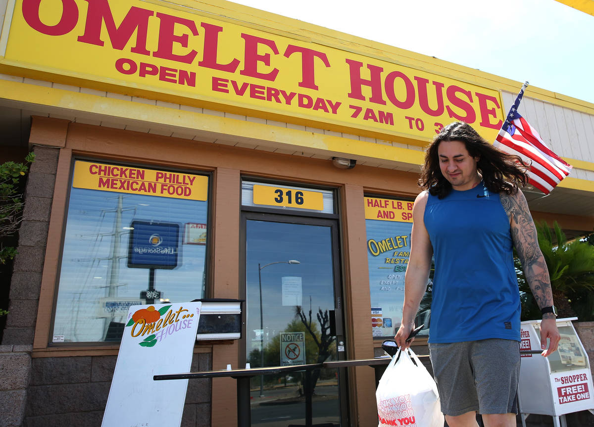 Aldo Salcedo picks up his order from a curbside pickup area at Omelet House on Wednesday, May 6 ...